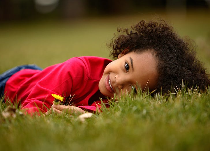 Adorable girl laying on grass smiling