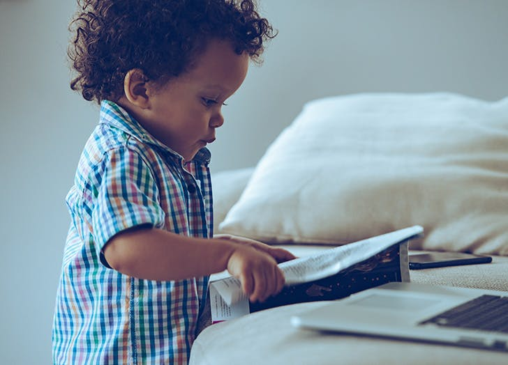 Baby boy looking through magazine