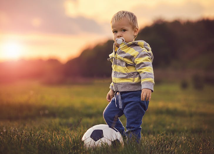 Baby boy playing soccer outside