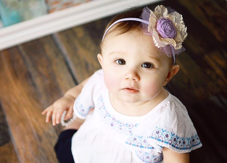 Baby girl looking up at camera with flower in her hair