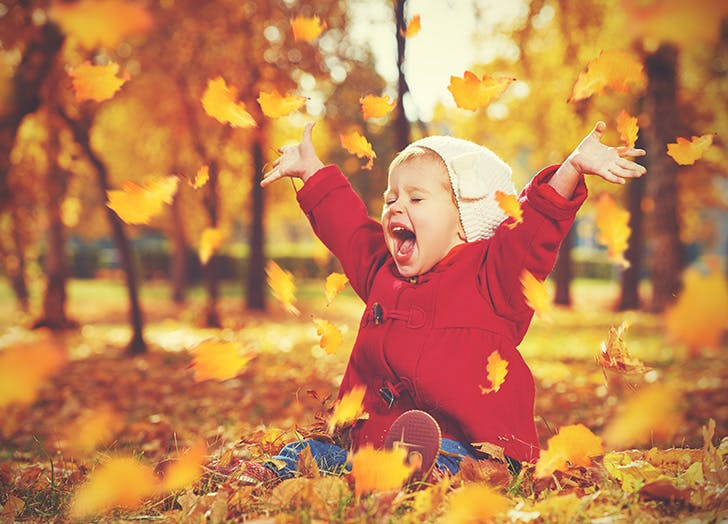 Baby girl playing with autumn leaves outside