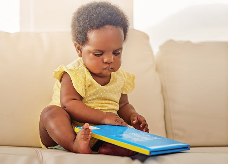 Baby girl sitting on the sofa reading a book