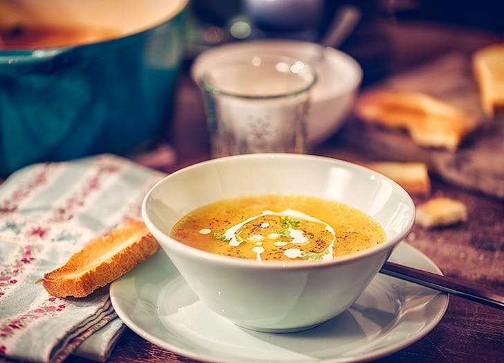 Bowl of carrot soup with crusty bread