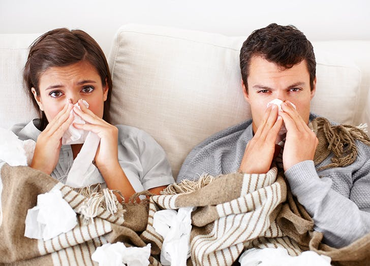 Couple sick in bed with the flu