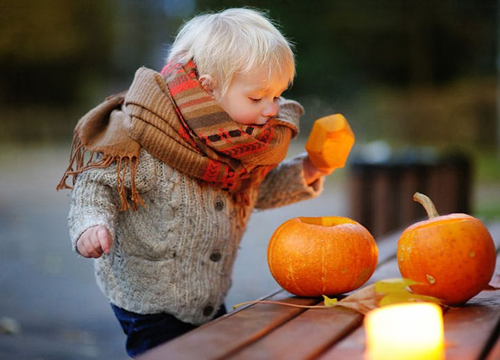 Cute October baby playing with pumpkins outside
