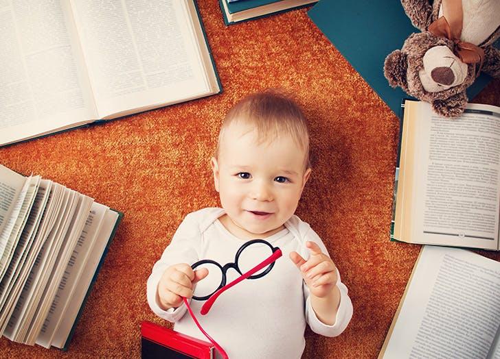 Cute baby boy lying on floor with books