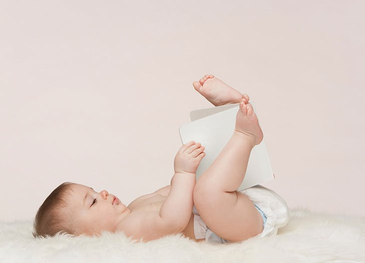 Cute baby girl lying on her back and playing with a book