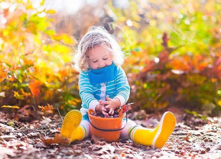 Cute girl playing outside with autumn leaves