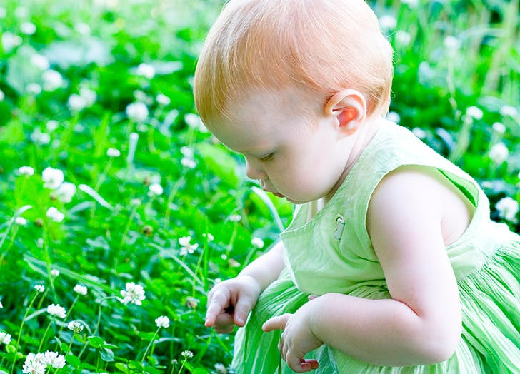 Cute little girl picking grass outside