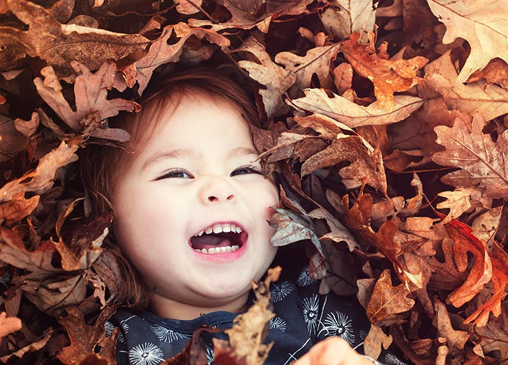 Happy toddler girl smiling while lying down in a big pile of leaves