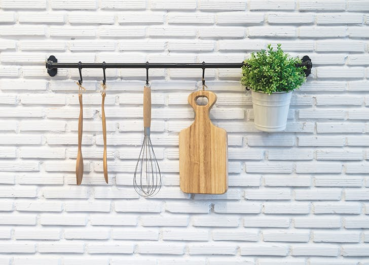 Kitchen utensils hanging up on white brick wall