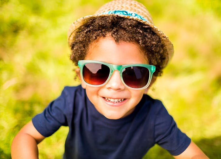 Little boy in sunglasses smiling at camera