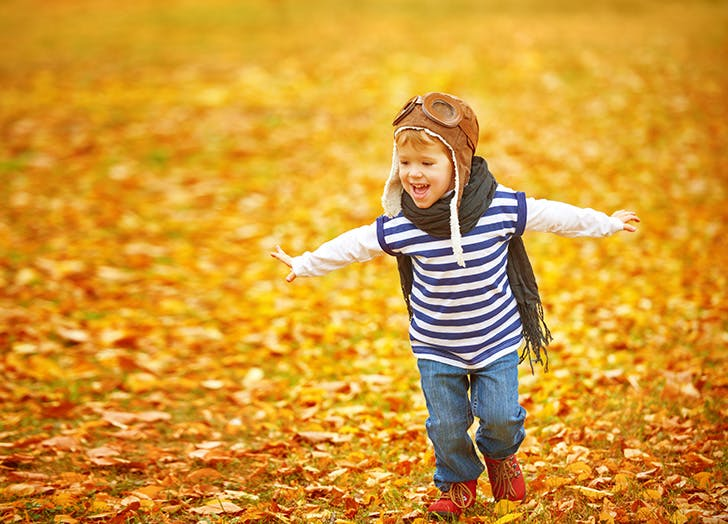 Little boy playing airplane outside in the fall