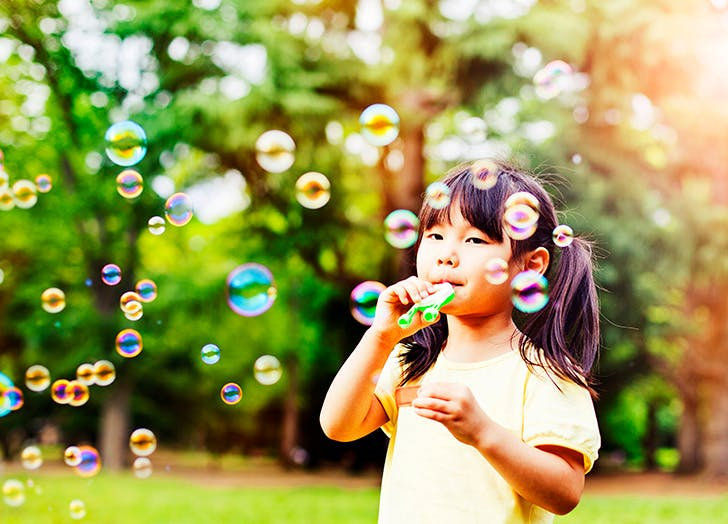 Little girl blowing bubbles outside