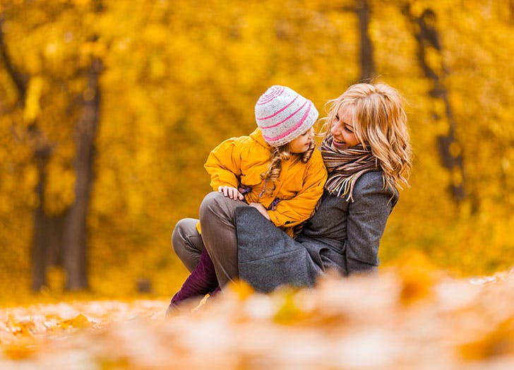 Mom and baby playing in autumn leaves