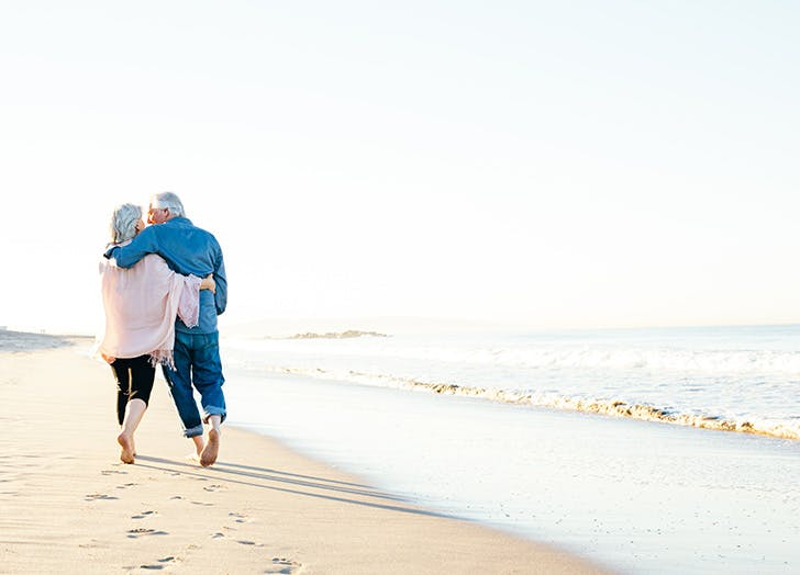 Older couple walking down the beach