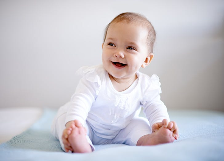 Smiling baby sitting on bed