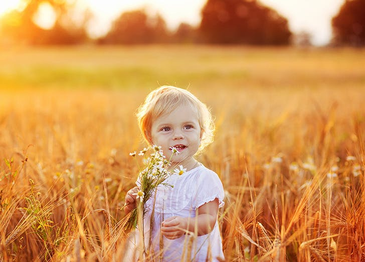 Sweet little girl outside in a field on a September day