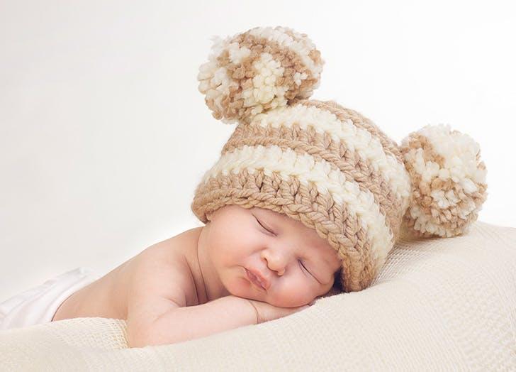 Sweet sleeping newborn with knitted pom pom hat