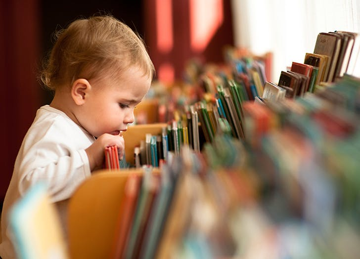 Toddler looking at books in library