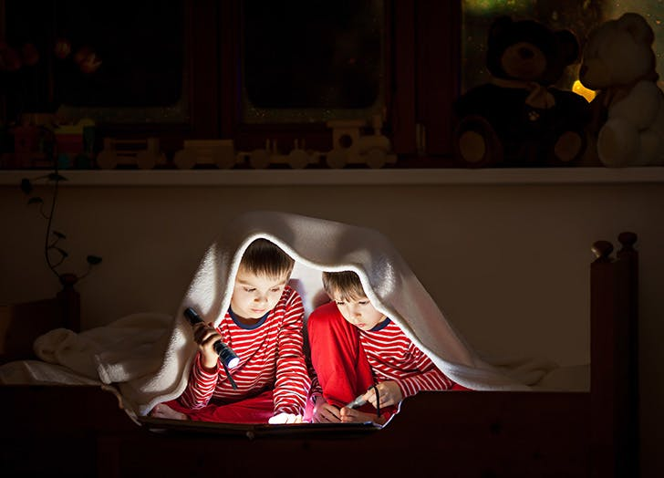 Two boys sharing a room and reading a book after dark