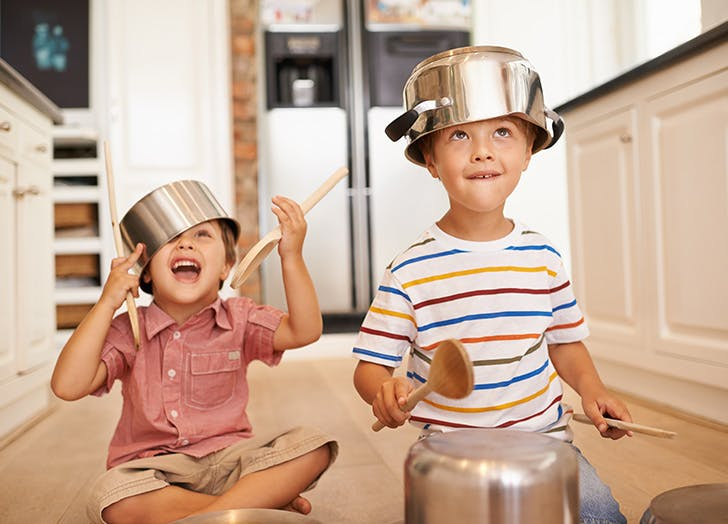 Two brothers playing on the kitchen floor with pots and pans