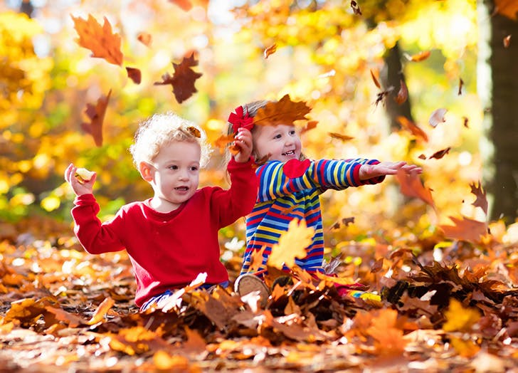Two siblings playing outside in fall leaves