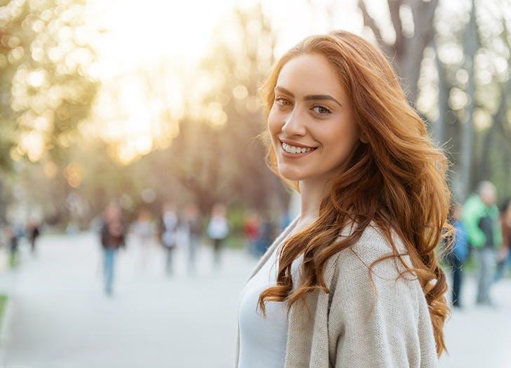 Woman walking outside and smiling at camera