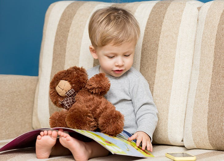 Young boy reading in chair with stuffed bear