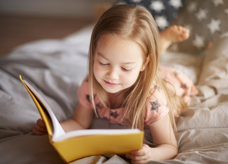 Young girl reading book in bed