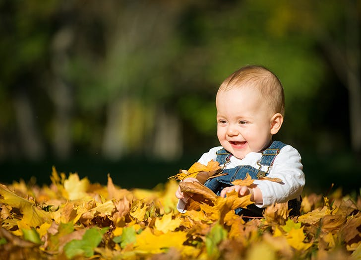baby boy playing outside with fall leaves