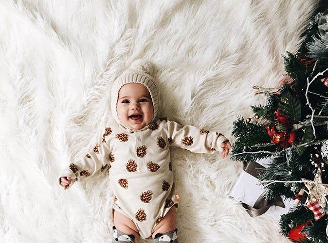 baby lying near christmas tree 501