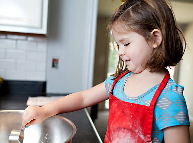 little girl baking red apron 501