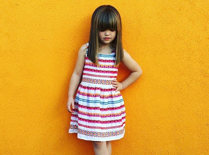 little girl in dress orange wall 501
