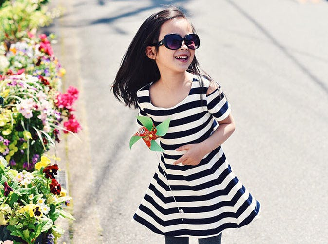 little girl in stripey dress sunglasses flowers 501