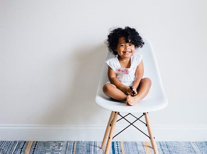 little girl on chair curly hair 501