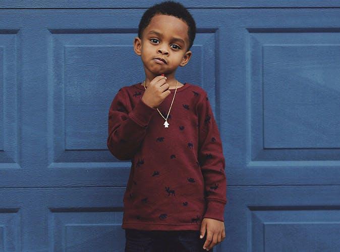 serious little boy against blue door 501