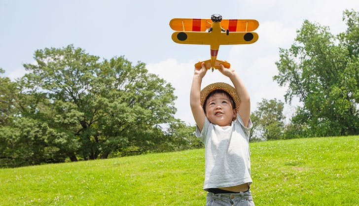 Boy playing with an airplane of toy in the park 1