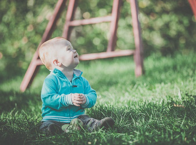 Cute Redhead Baby Boy Playing in Grass in Apple Orchards