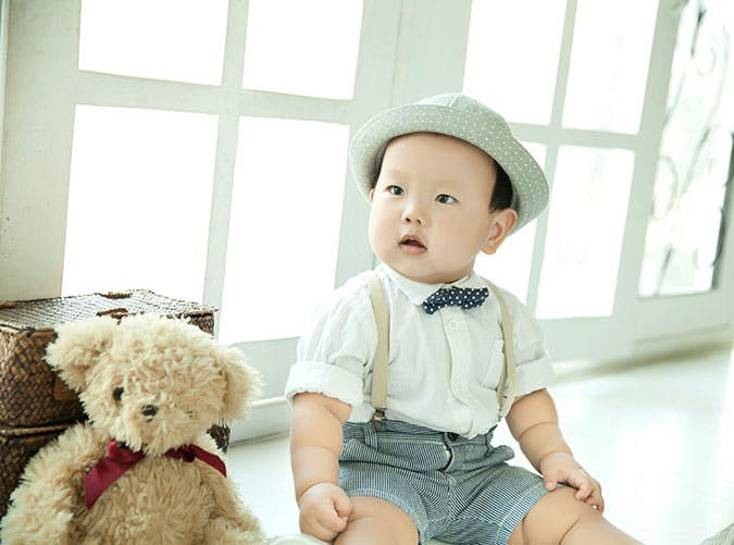 Cute baby boy dressed up and sitting with teddy bear