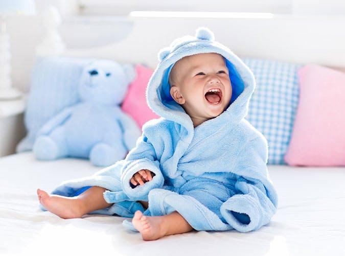 Cute baby boy in bath robe sitting on bed