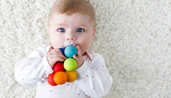 Cute baby boy playing with colorful wooden rattle toy