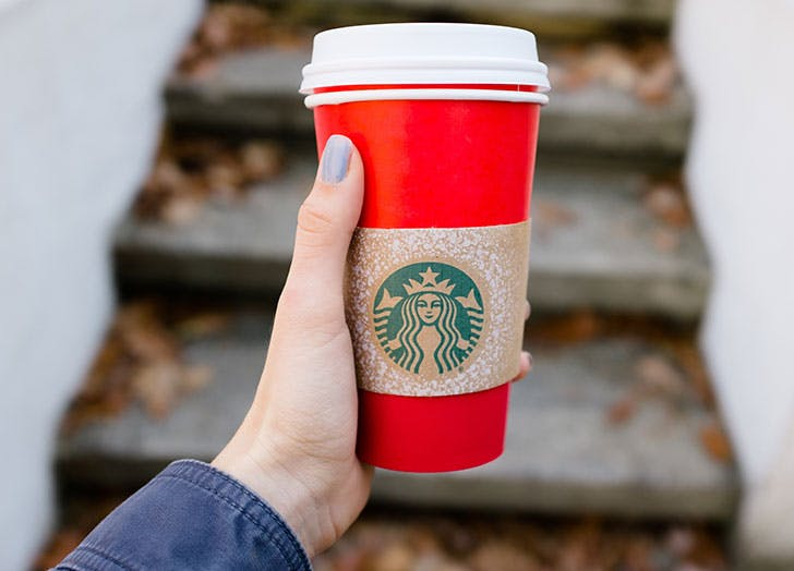 Hand holding out a Christmas Starbucks cup