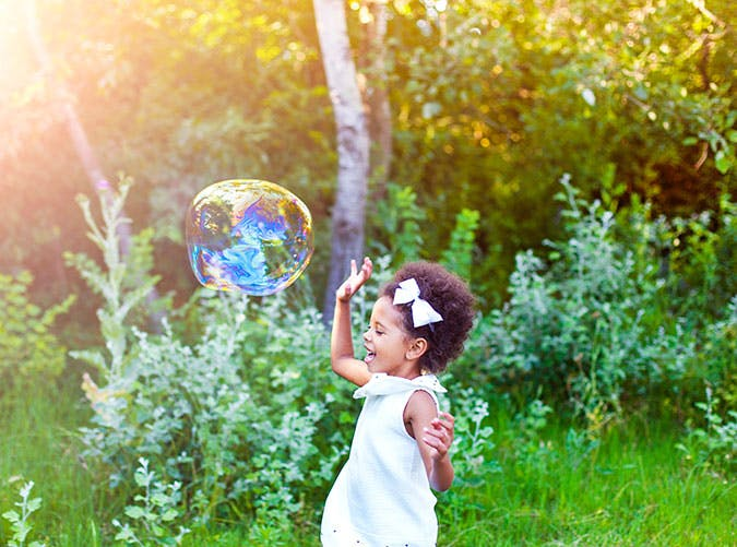 Happy little girl playing soap bubbles in park