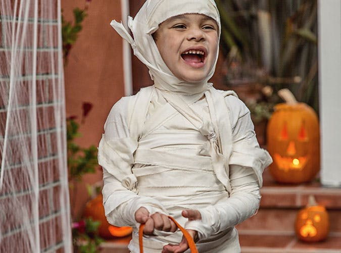 Kid dressed up as a mummy for Halloween