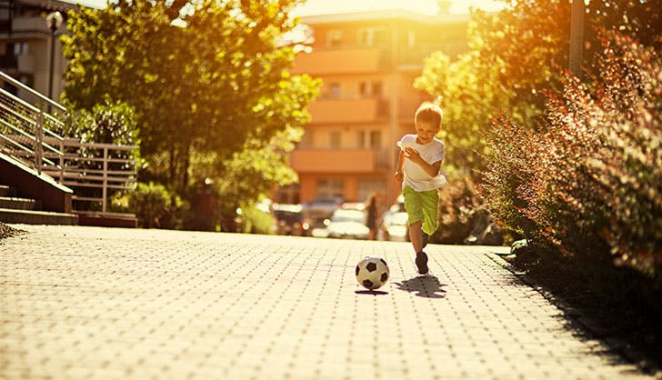 Little Spanish boy playing soccer on the street