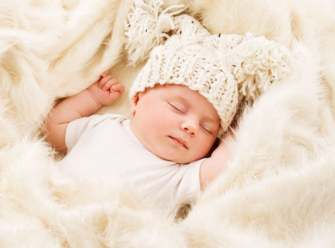 Newborn baby sleepign in a white hat