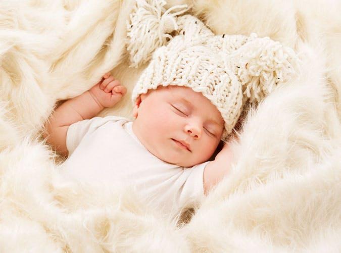 Newborn baby sleepign in a white hat
