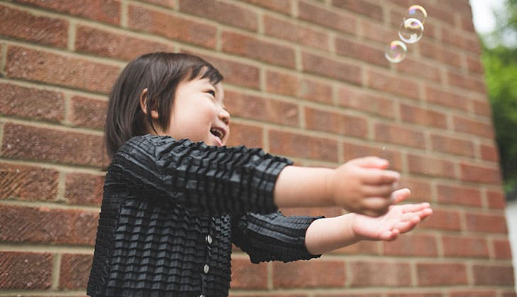 Petit Pli expandable clothing child playing with bubbles