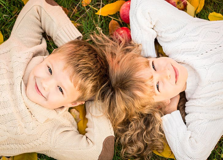 Two cute kids lying on the November grass outside